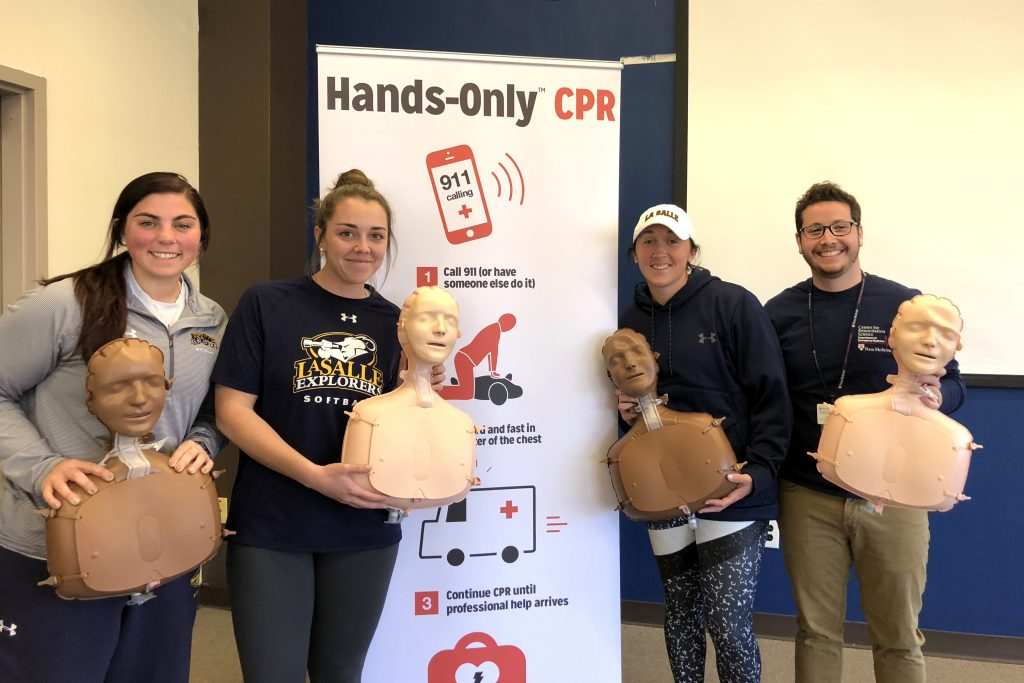 Four people pose with CPR training dummies at La Salle University