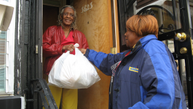 A MANNA client receives a food delivery at her doorstep.