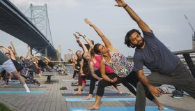 A group of yogis practice side angle post at Race Street Pier. Photo is taken facing the Delaware River with the Ben Franklin Bridge in the background