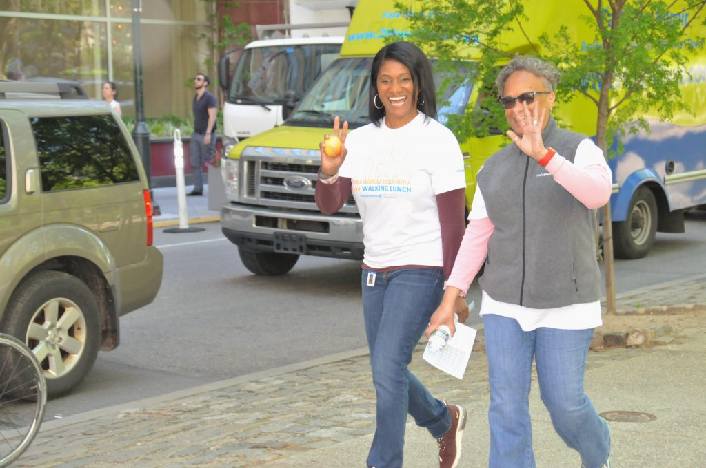 two Independence Blue Cross associate smile and wave to the camera as they walk the perimeter of Rittenhouse Square Park on National Walk at Lunch Day 2019