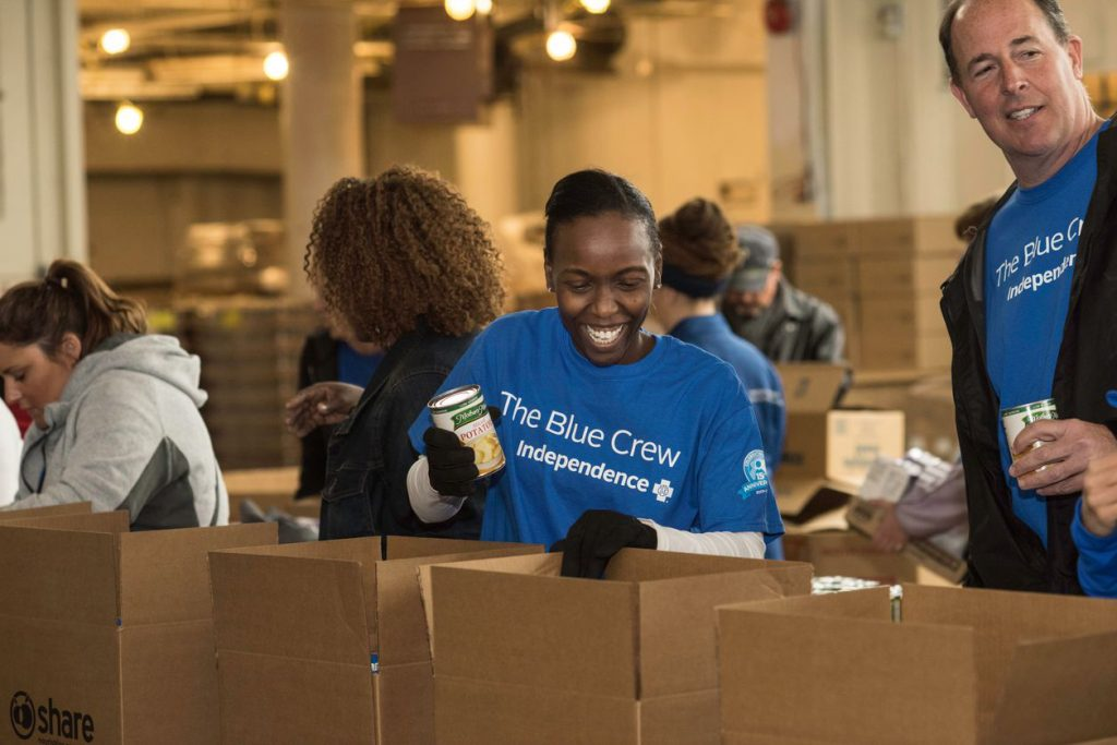 Photo of Blue Crew volunteers smiling while packing boxes of canned food at Share Food Program Location