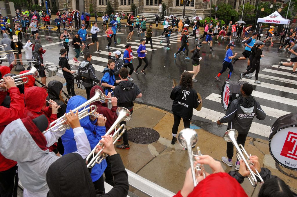2019 Blue Cross Broad Street runners pass the Temple University marching band