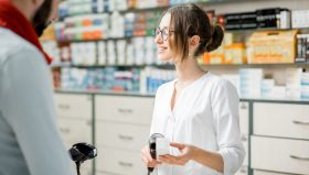 Young woman pharmacist selling medications standing with male client at the paydesk of the pharmacy store