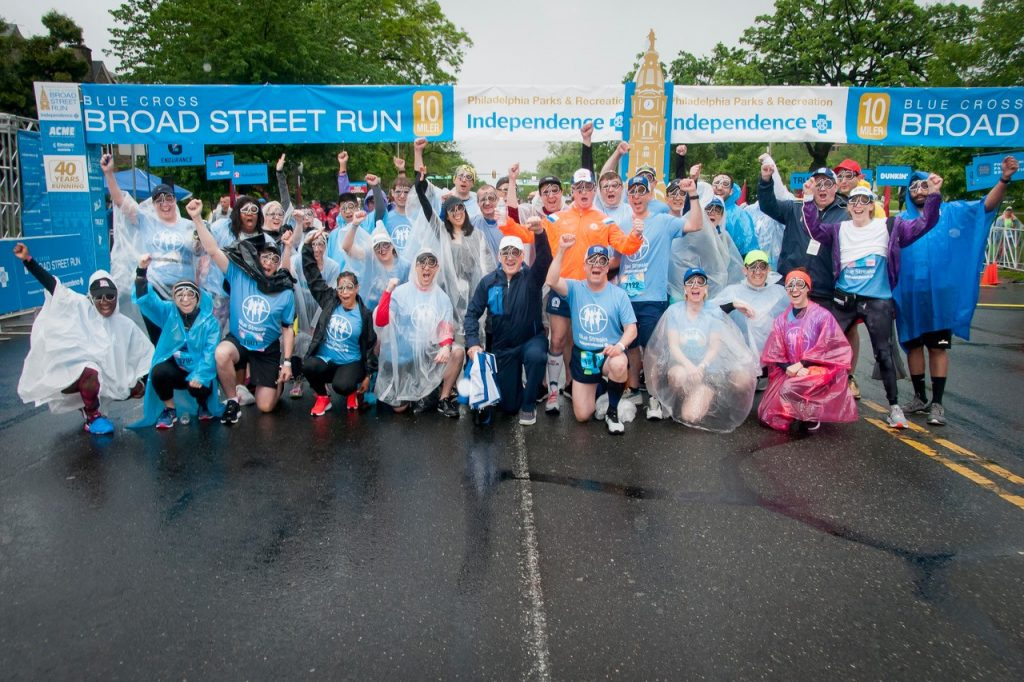 IBX Blue Streaks team photo at the 2019 Blue Cross Broad Street Run start line. Team members are wearing novelty glass in the shape of the number 40