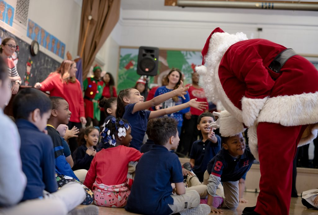 Photo of Santa greeting children at the Sheppard School in Kensington, Philadelphia during Independence's annual holiday celebration at the elementary scholol