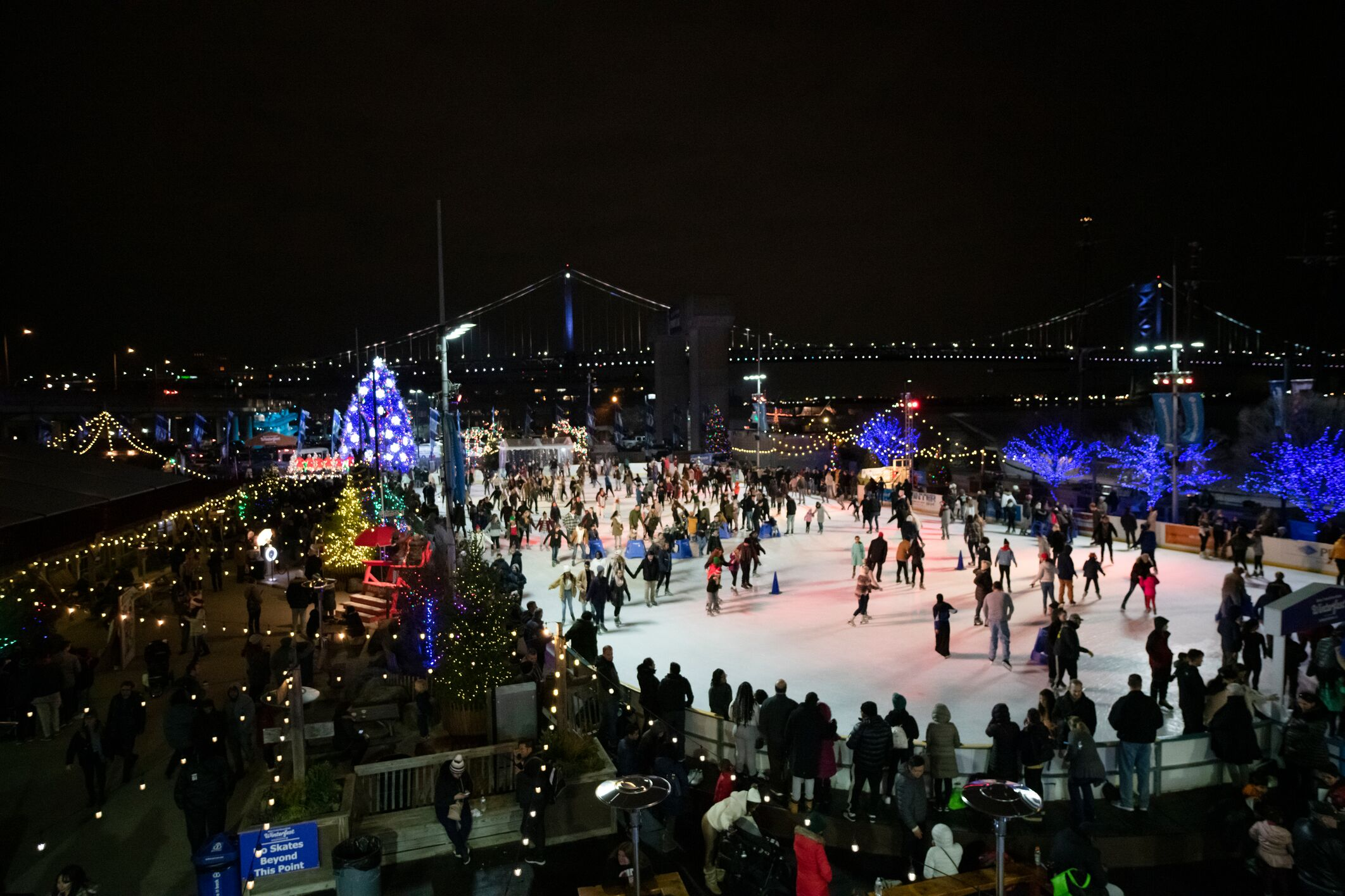 Image of Blue Cross RiverRink Winterfest depicts the waterfront ice skating rink with views of the Ben Franklin Bridge