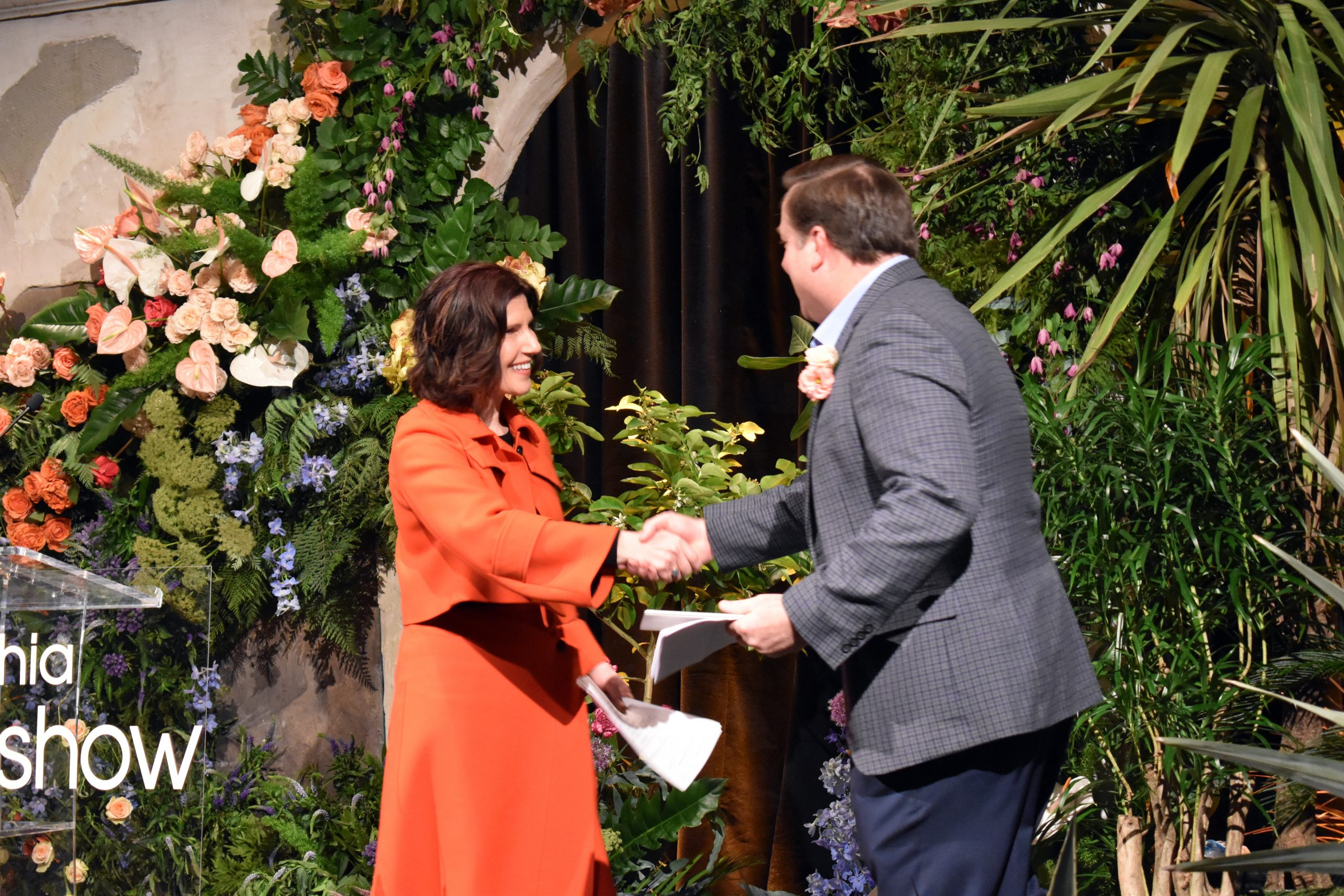 Shows Daphne Klausner on stage shaking hands with representative from the Philadelphia Horticultural Society at press event