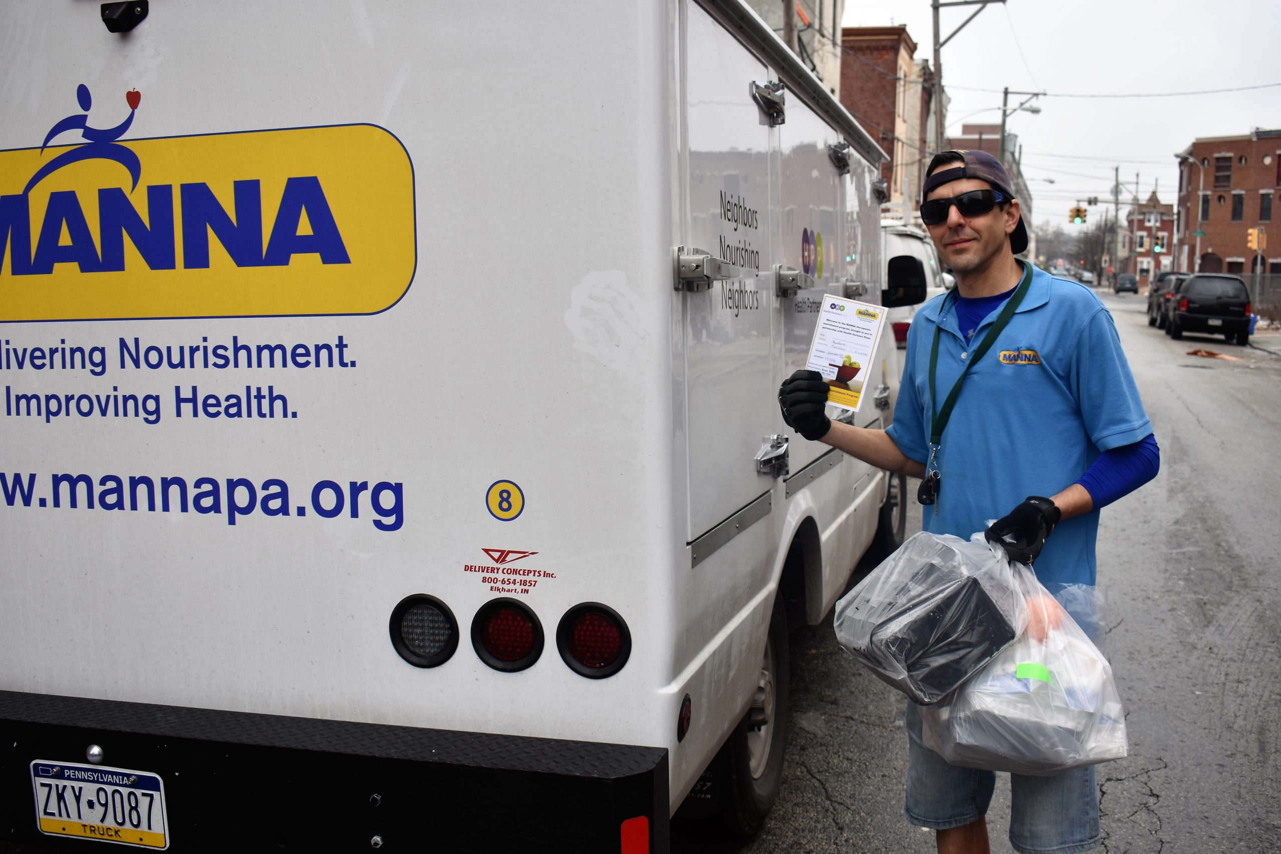 MANNA food delivery driver pictured next to a truck with the MANNA logo