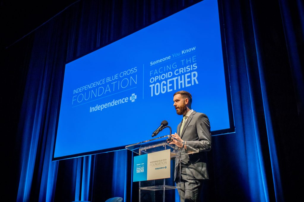 Image of Independence Blue Cross associate, Patrick Flynn, speaking on stage about his recovery journey