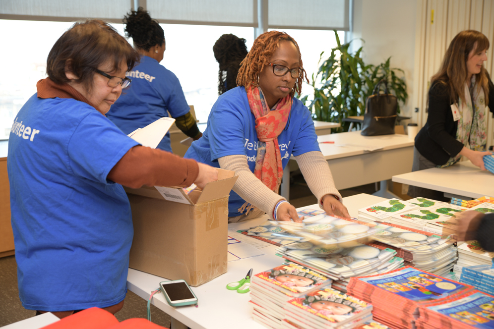 Blue Crew volunteers in blue t-shirts pack up books for children
