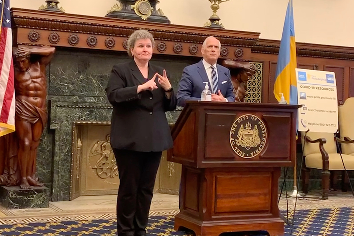 IBX CEO Dan Hilferty stands behind the podium at the COVID-19 Fund announcement at City Hall. A female American Sign Language interpreter stands to his right