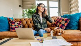 woman working from home in the company of her puppy making calls of kindness