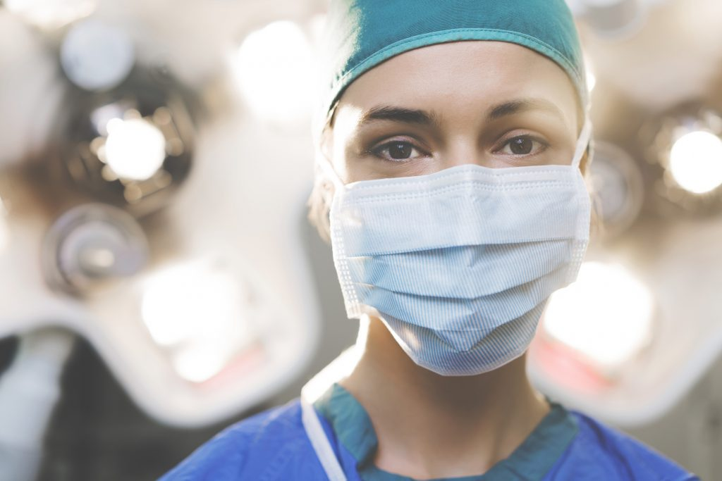 portrait of a female surgeon. Healthcare worker is wearing surgical mask. She is against illuminated lights in operating room at hospital.