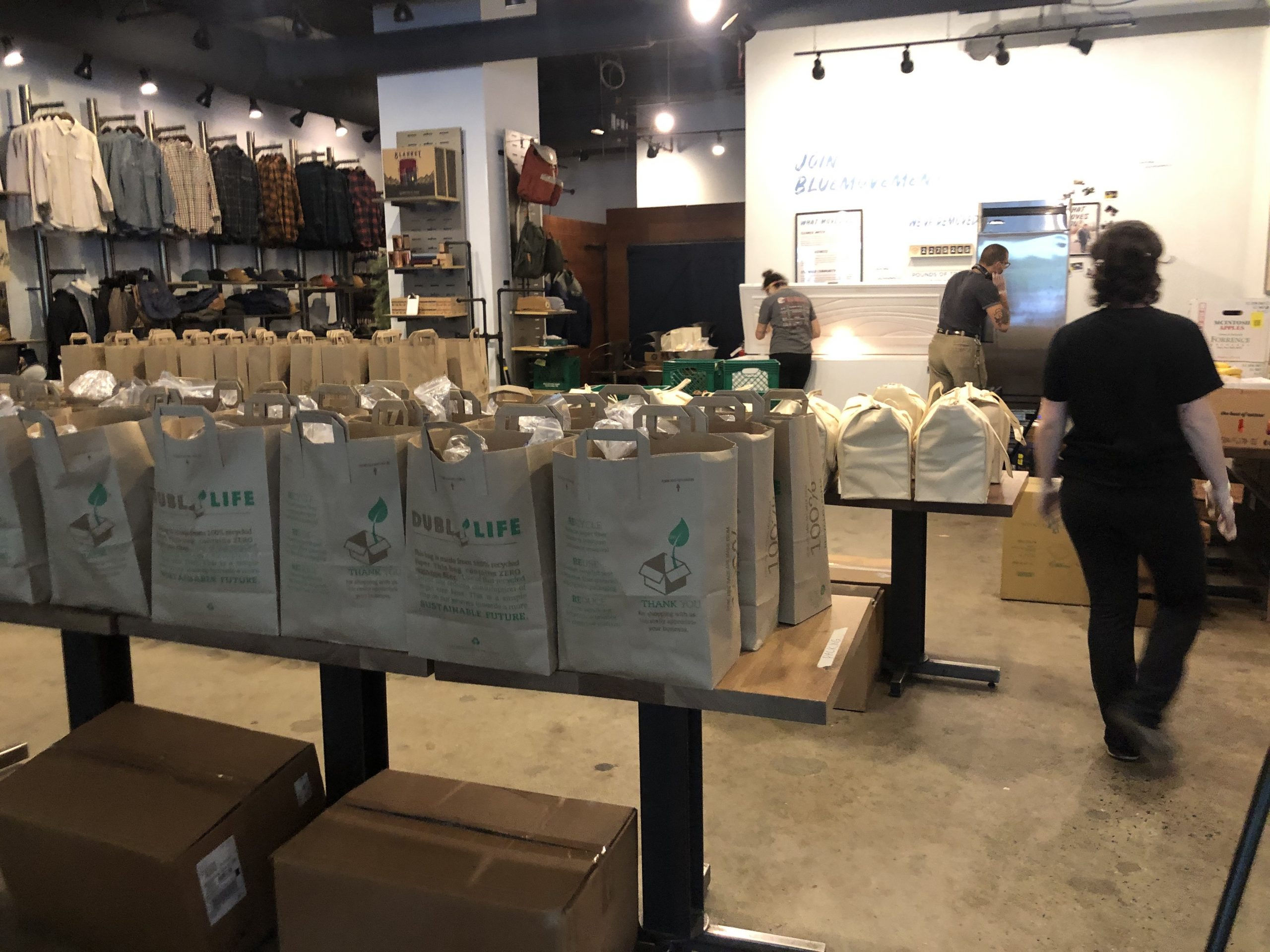 paper and canvas grocery bags lined up on several tables at United By Blue. Clothing hangs in the background of the store
