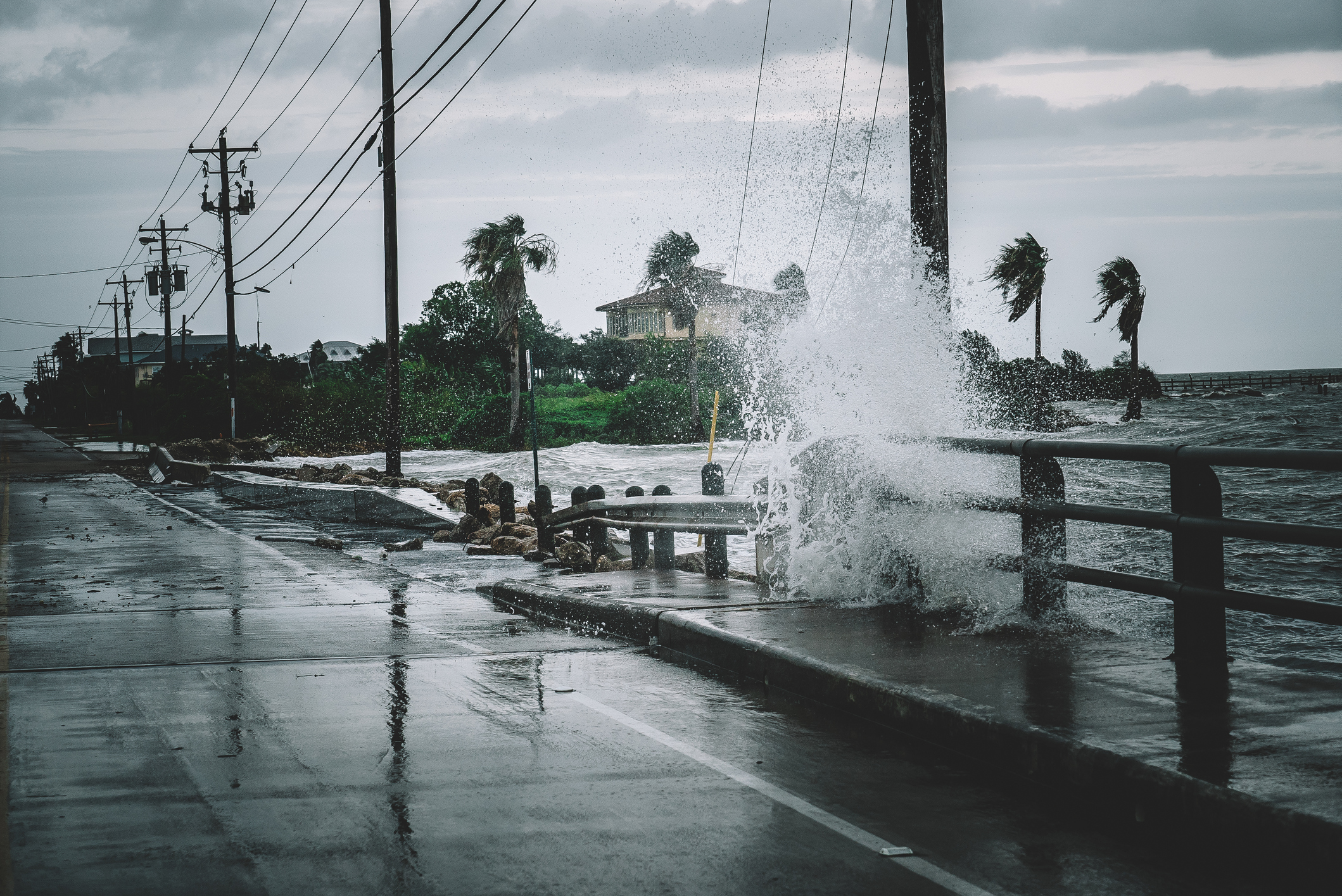 A wave crashes over a street railing during a hurricane in Texas