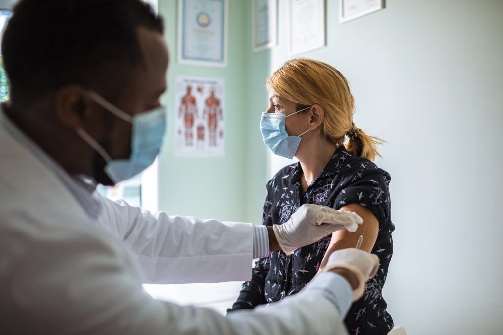 Woman with strawberry-blonde hair wearing a blue face mask getting vaccinated