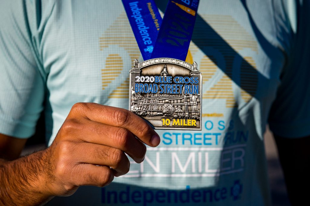 close up of the 2020 Blue Cross Broad Street Run medal in front of a light blue 2020 race shirt