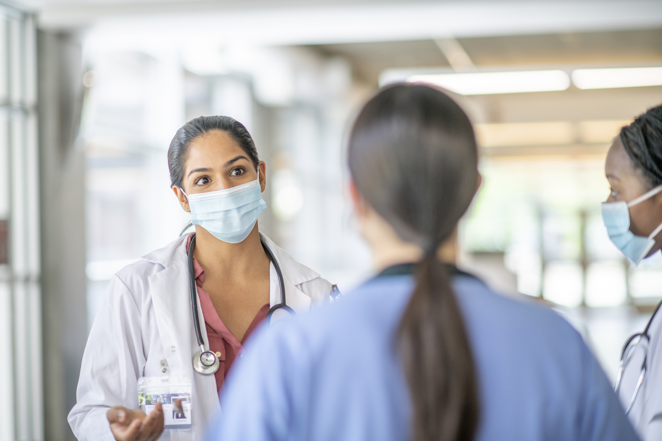 three health care professionals in masks consulting in a hallway