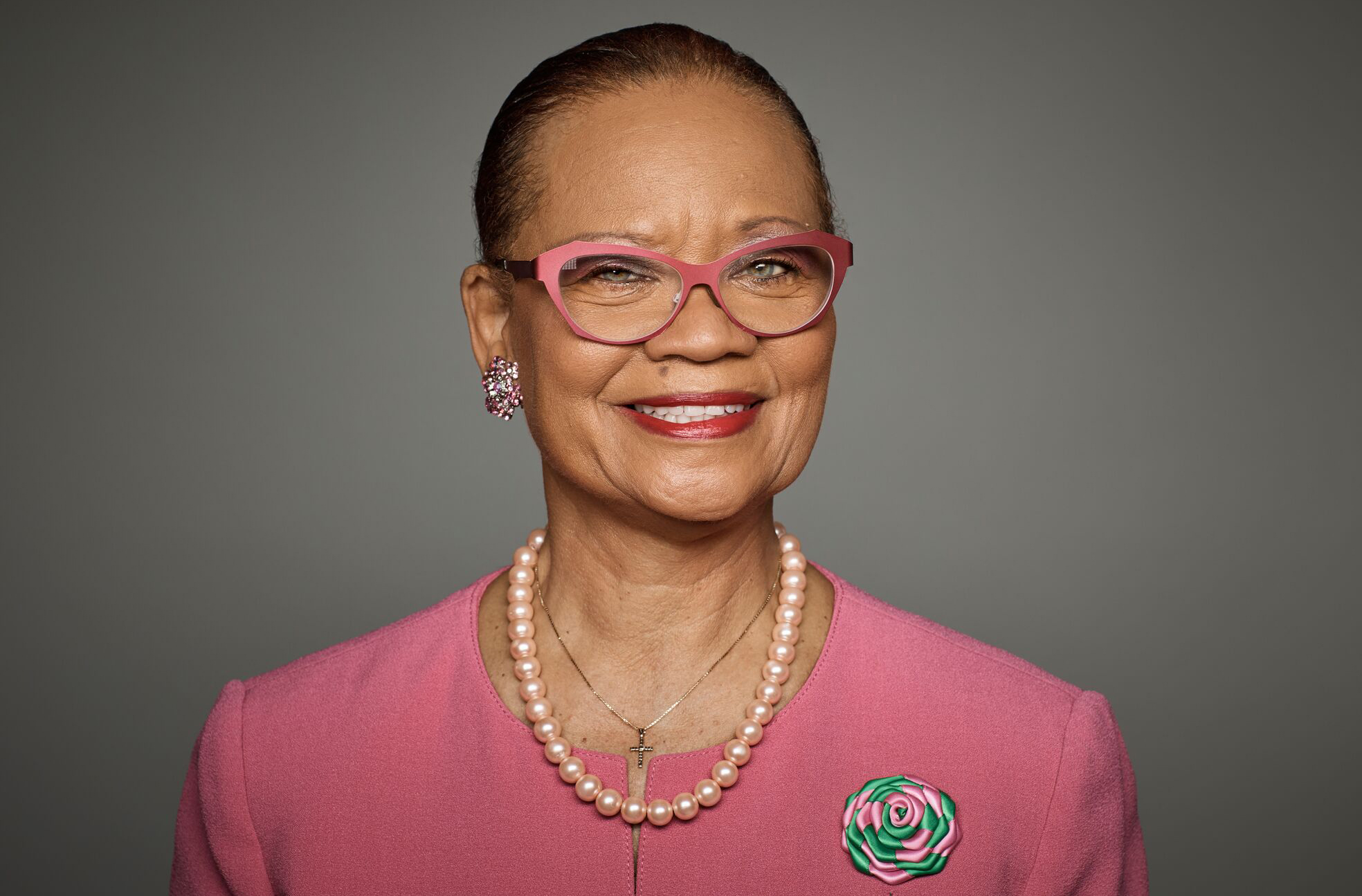 Headshot of Lorina Marshall-Blake wearing pink glasses, a pink jacket, and pearls