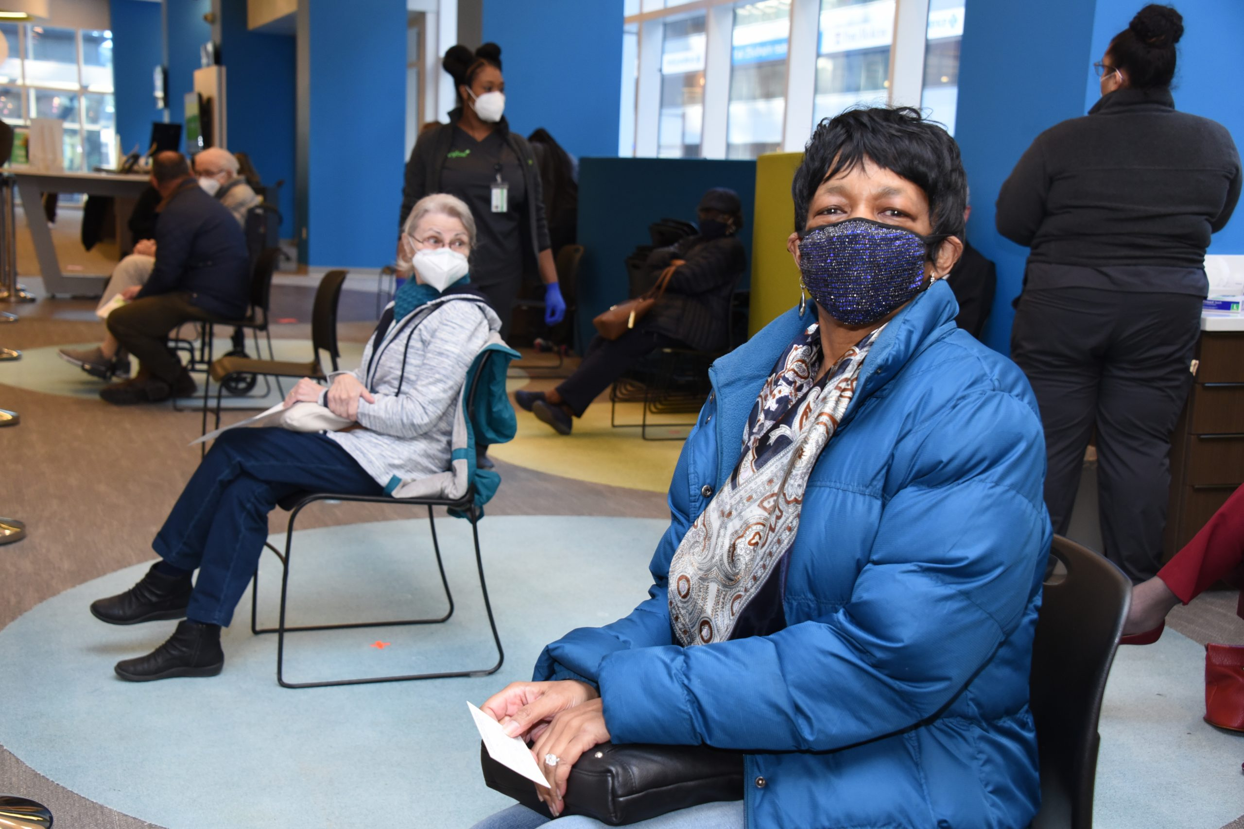 Philadelphia resident in mask smiles at camera while waiting for her COVID-19 at Independence LIVE